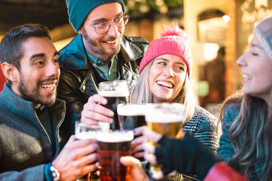 Friends drinking beer at brewery bar outdoor on winter time - Friendship concept with young people having fun together toasting at happy hour promotion - Focus on girl with pink hat - Warm neon filter