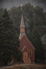 Picturesque mountain chapel surrounded by old growth forest trees