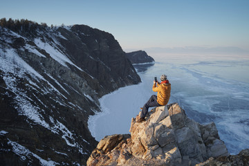 Lake Baikal at winter. Man sitting on a cliff and taking photo on smartphone. Frozen Baikal lake. Deepest and largest fresh water lake. Olkhon Island, Russia, Siberia.