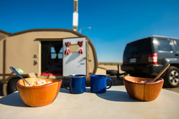 Selective focus of two wooden bowls of food and two cups of coffee or tea standing on a small table in front of a caravan