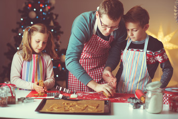 Happy father with his children bakes ginger cookies for Christmas with christmas tree on background