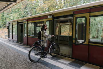 Woman with bicycle entering an underground train, Berlin, Germany