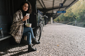 Woman with bicycle having lunch and using smartphone on station platform, Berlin, Germany Wall mural