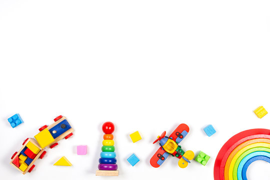 Baby kids toys background. Wooden train, rainbow stacker, red plane, stacking rings tower pyramid toy and colorful blocks. Top view, flat lay