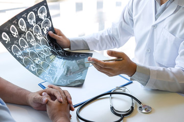Doctor holding and looking at x-ray film examining at brain by ct scan of patient and analyze result while discussing explaining problem of medical