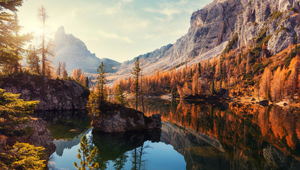 Amazing Federa lake, natural Scenery, during Sunrise. Awesome Landscape. Foggy Dolomites Alps with forest under sunlight. Travel in nature. Beautiful sunrise with Lake and majestic Mountains