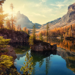 Wonderful Federa lake, natural Scenery, during Sunrise. Awesome Landscape. Foggy Dolomites Alps with forest under sunlight. Travel in nature. Beautiful sunrise with Lake and majestic Mountains.