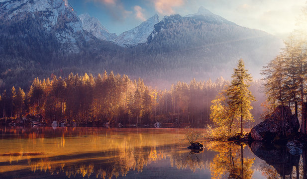 Awesome Nature Scenery. Beautiful landscape with high mountains with illuminated peaks, stones in mountain lake, reflection, blue sky and yellow sunlight in sunrise. Amazing nature Background.