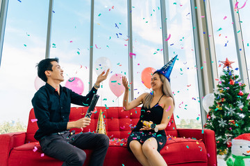 Excited Asian man and woman laughing and catching confetti from petard while sitting on sofa against window and having fun on Christmas party together