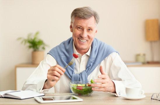 Senior Man Eating Vegetable Salad Smiling At Workplace Indoor