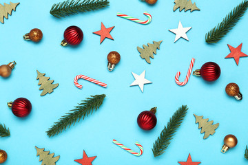 Flat lay christmas composition. Different ornaments with fir tree branches on blue background