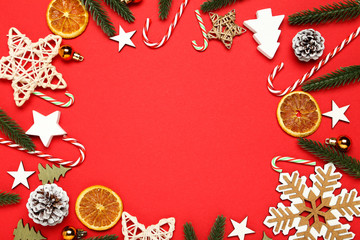 Flat lay christmas composition. Candy canes, ornaments, dry oranges and fir tree branches on red...
