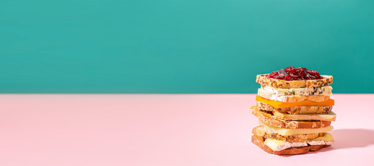 Photo sur Aluminium Snack horizontal banner of a Big Sandwich with french cheese toast and jam on a pink and green background