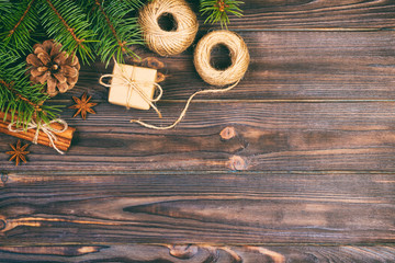 Wall Mural - Christmas background or Holiday greeting card. christmas present box with fir tree branch and decorations on wooden table. Top view with copy space. Toned