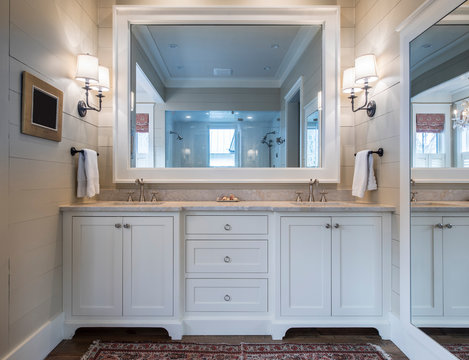 Beautiful bathroom interior with double sinks and marble counter, and large mirrors.