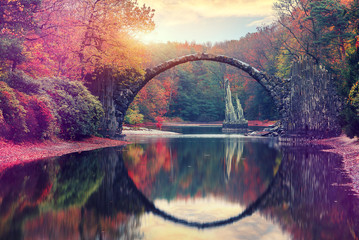 Photo sur Plexiglas Ponts Awesome Autumn Landscape. Amazing sunset in Azalea and Rhododendron Park Kromlau. Rakotz Bridge, Rakotzbrucke Devil's Bridge in Kromlau, Saxony, Germany. Creative Artistic image.