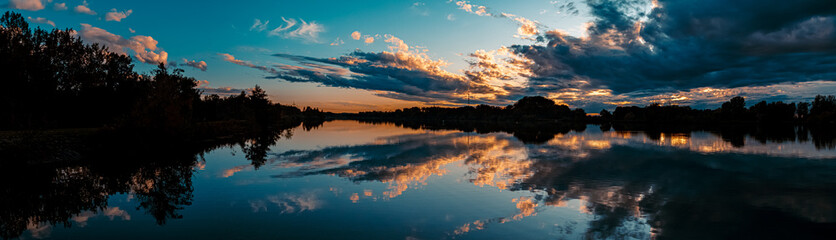 High resolution stitched panorama of a beautiful sunset with arrow-shaped reflections near Plattling, Isar, Bavaria, Germany