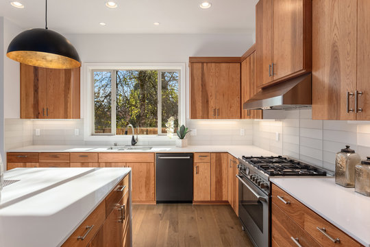 Kitchen detail featuring stainless steel oven, cooktop, and dishwasher, quartz counters, sink, cabinets, and window