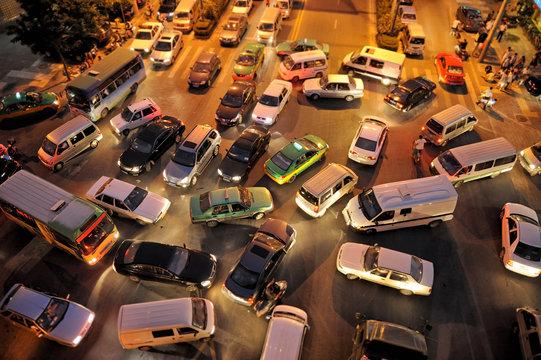 Messy traffic at crossroad at night, aerial view
