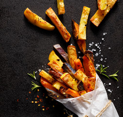 French fries,  baked fries from different types and colors of potatoes sprinkled with herbs and spices in paper bag on a black background, top view, close-up.
