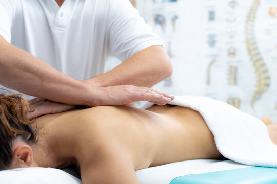 Young woman receiving shoulder massage in a physiotherapy center