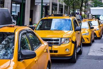 Row of yellow taxis from New York City on the street. Concept of transport and travel. Manhattan, New York, USA