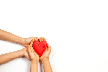 Adult and child hands holding red heart over white background. Love, healthcare, family, insurance, donation concept