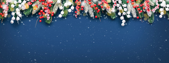 Christmas banner with fir branches and decorations on blue background with snow.