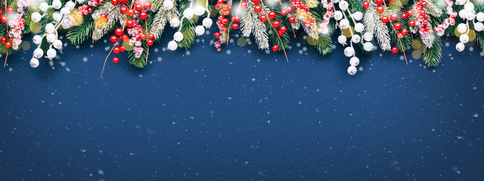 Christmas banner with fir branches and white and red decorations on blue background with snow.