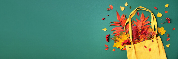 Autumn flat lay composition. Dry maple autumn leaves in yellow shopping bag on green background. Top view. Copy space. Flat lay.