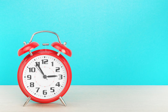 Red retro alarm clock with five minutes to three o'clock, on wooden table on a blue background. The concept of time, holiday, 5 minutes to the event, deadline. Layout with copy space for your text.