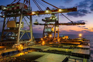 Cranes in the port for unloading cargo from ships. Cranes unloading coal from Ship. Night view.. Wall mural