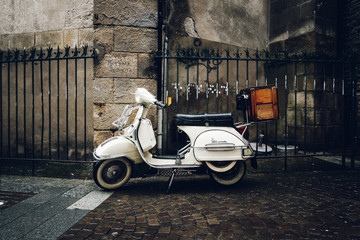 A vintage Vespa scooter parked in the street by a rainy day, in Nantes, France.