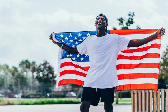 Serious African American man holding American flag on shoulder and looking away