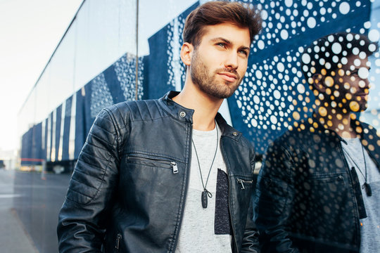 Confident fashionable male in casual stylish outfit leaning on modern glasses wall and looking away