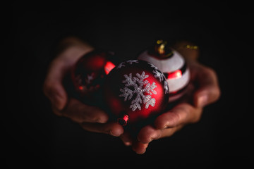 Closeup anonymous person demonstrating handful of decorated Christmas balls against black background