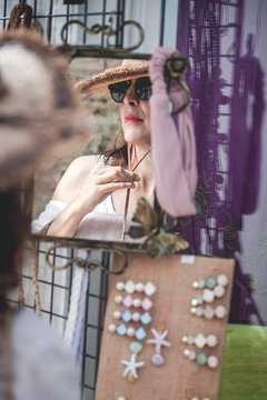 Stylish confident woman in sunglasses looking in reflection of small mirror for checking straw hat with cord at town market