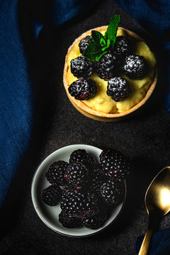 Homemade small cake with blackberry and delicious cream of vanilla and mint on dark background