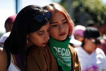 Women react as they watch pictures of violence victims during a protest to commemorate International Day for the Elimination of Violence against Women in San Salvador
