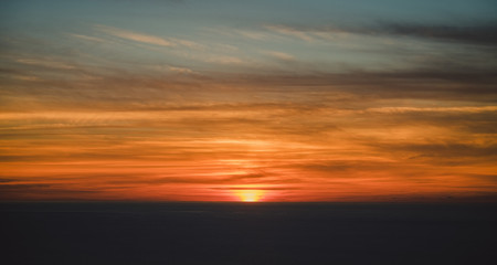 From above blurred gray horizon with hiding sun under beautiful colorful clouds on sky with wonderful transition at dusk