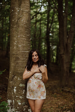 Shy sensual woman standing on stone in forest