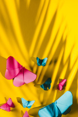 Fragile butterflies made of paper with palm tree leaf shadow attached to yellow cardboard background