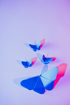 Pink and blue butterflies attached to lilac wall over carved paper leaf