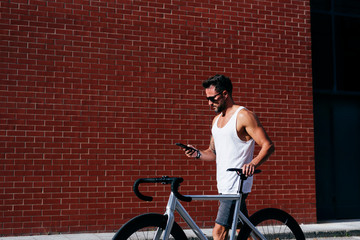 Side view of handsome male cyclist in sportswear and sunglasses using smartphone while standing with bike next to red brick wall