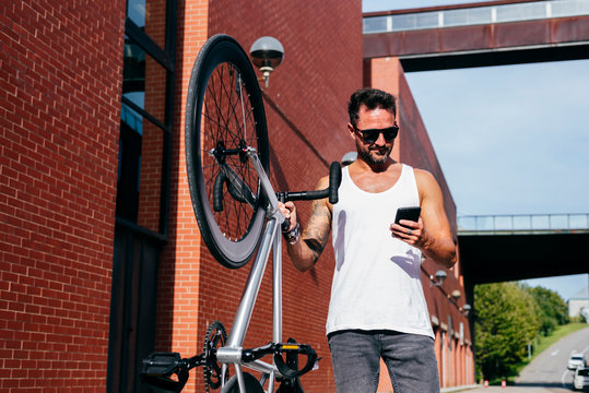 Handsome male cyclist in sportswear and sunglasses using smartphone while standing with lifting bike next to red brick wall