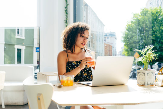 Ethnic woman with curly hair drinking fresh juice and using laptop while sitting against window in modern stylish restaurant