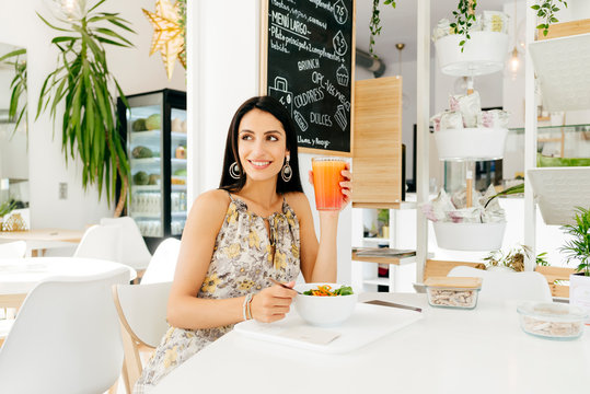 Cheerful woman with healthy food in cafe