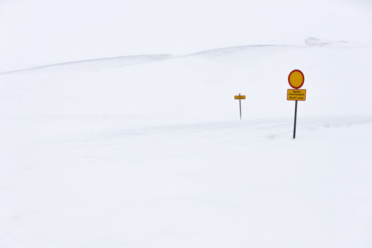Red and yellow caution signposts located in middle of snowy nature on cold winter day in Iceland