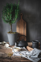 Composition of black teapot and white bowl and chamomile herbs on wooden table