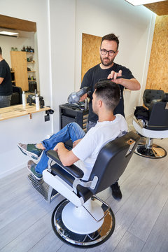 Stock vertical photo of a barber drying his hair with a comb and a hairdryer in front of the mirror. Barber shop
